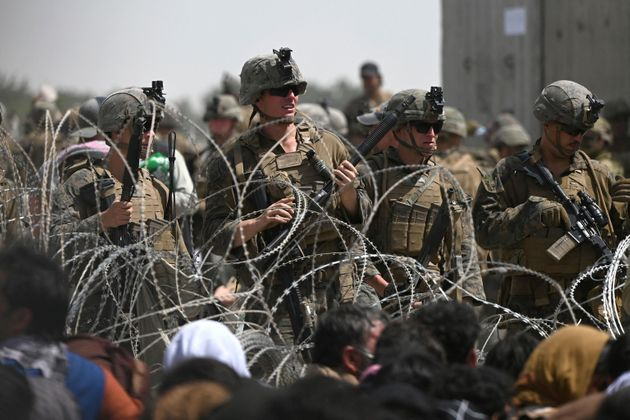 TOPSHOT - US soldiers stand guard behind barbed wire as Afghans sit on a roadside near the military part of the airport in Kabul on August 20, 2021, hoping to flee from the country after the Taliban's military takeover of Afghanistan. (Photo by Wakil KOHSAR / AFP)