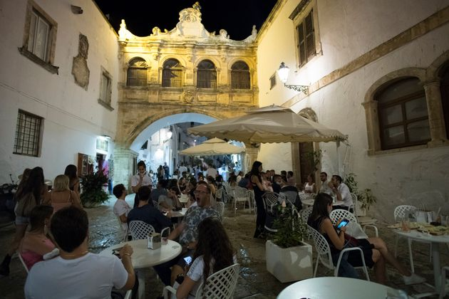 OSTUNI, ITALY - AUGUST 12: General view of people wearing protective masks sitting in the dehor of a restaurant in Piazza Beato Giovanni Paolo II in the Ostuni nightlife on August 12, 2020 in Ostuni, Italy. Tourism in the Puglia Region was very active in the summer on the beaches, towns and clubs of the city center, despite the danger of Covid 19, Italians and tourists in general respected the Covid-19 prevention measures. (Photo by Stefano Guidi/Getty Images)