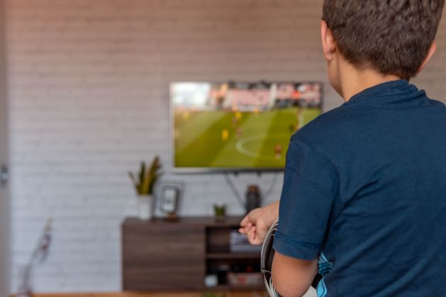 Rear view of boy watching TV at home. Boy watching soccer or football game on