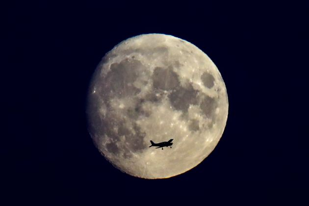 NOVOSIBIRSK, RUSSIA AUGUST 20, 2021: A plane flying by a nearly full moon. Kirill Kukhmar/TASS (Photo by Kirill Kukhmar\TASS via Getty Images)