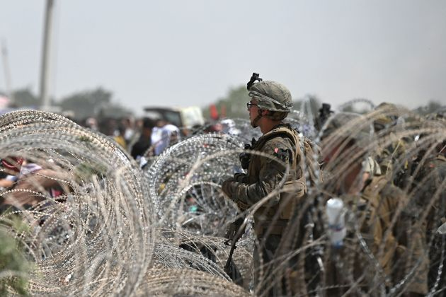 A US soldier stands on guard as Afghans gather on a roadside near the military part of the airport in...