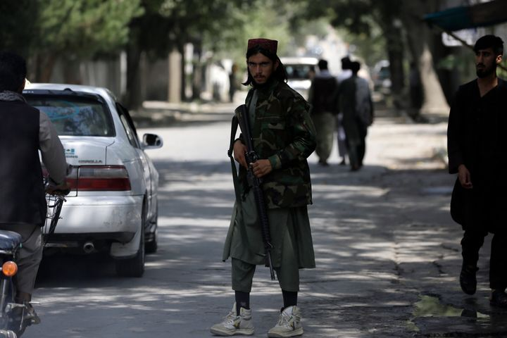 A Taliban fighter stands guard at a checkpoint in the Wazir Akbar Khan neighborhood in the city of Kabul on Sunday.