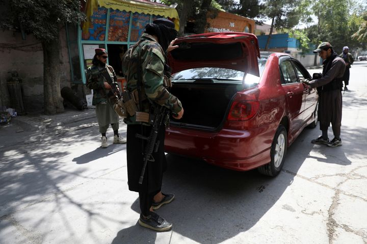 Taliban fighters search a vehicle at a checkpoint on a road in the Wazir Akbar Khan neighborhood on Sunday.