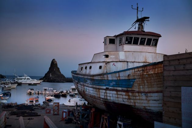 Fishing boat under repair in shipyard in Acitrezza, with famous sea stack in the background. Sicily, Italy
