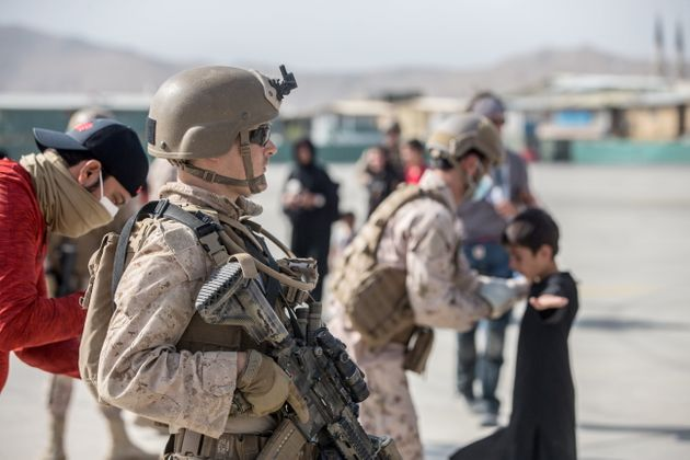 A U.S. Marine provides assistance during an evacuation at Hamid Karzai International Airport, Kabul,...