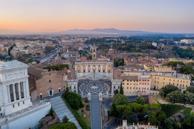Aerial view of the Piazza del Campidoglio with Colosseum and City Buildings on background, Rome.