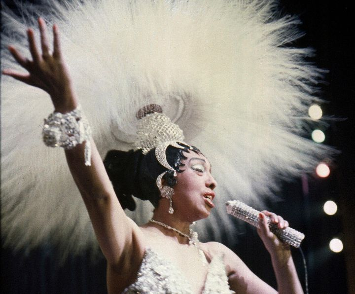 """Josephine Baker holds a rhinestone-studded microphone as she performs during her show """"Paris, mes Amours"""" at the Olympia Music Hall in Paris on May 27, 1957."""