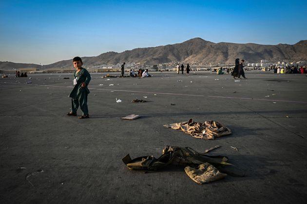Un niño afgano camina junto a uniformes del ejército local, cerca del aeropuerto de Kabul,...