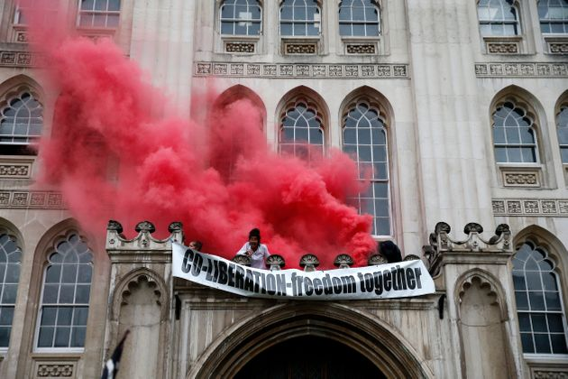 Protesters from Extinction Rebellion light a flare and unfurl a banner from the Guildhall on August 22,...