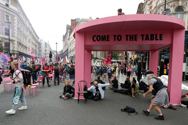 People participate in a protest of Extinction Rebellion climate activists next to a big model table,...