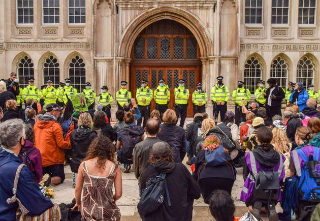 Protesters kneel down while police officers guard the Guildhall building entrance during the