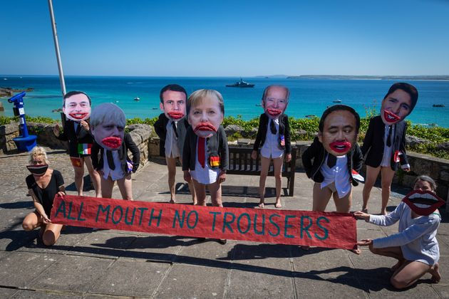 Extinction Rebellion protesters wearing cartoon heads of the G7 leaders pose with a banner reading
