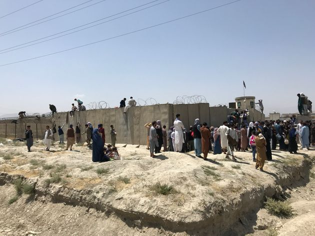 People struggle to cross the boundary wall of Hamid Karzai International Airport to flee the country after rumors that foreign countries are evacuating people even without visas, after the Taliban over run of Kabul, Afghanistan, 16 August 2021. (Photo by STR/NurPhoto via Getty Images)