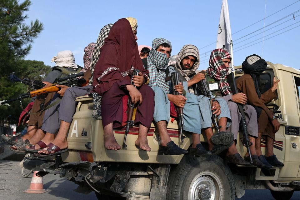 Taliban fighters in a vehicle patrol the streets of Kabul on August 23,