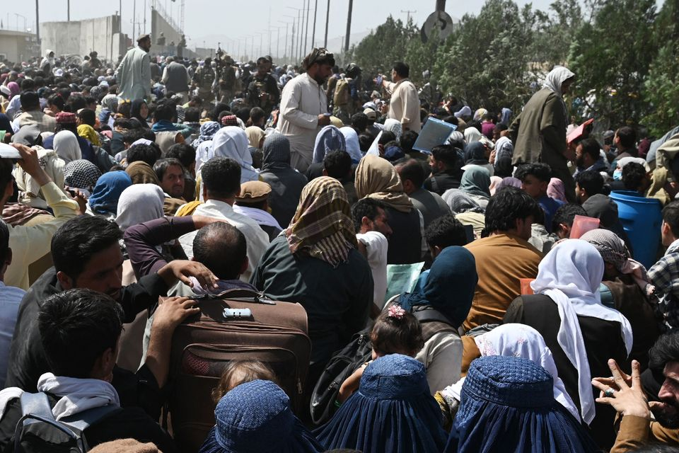 Afghans gather on a roadside near the military part of the airport in Kabul on August 20,
