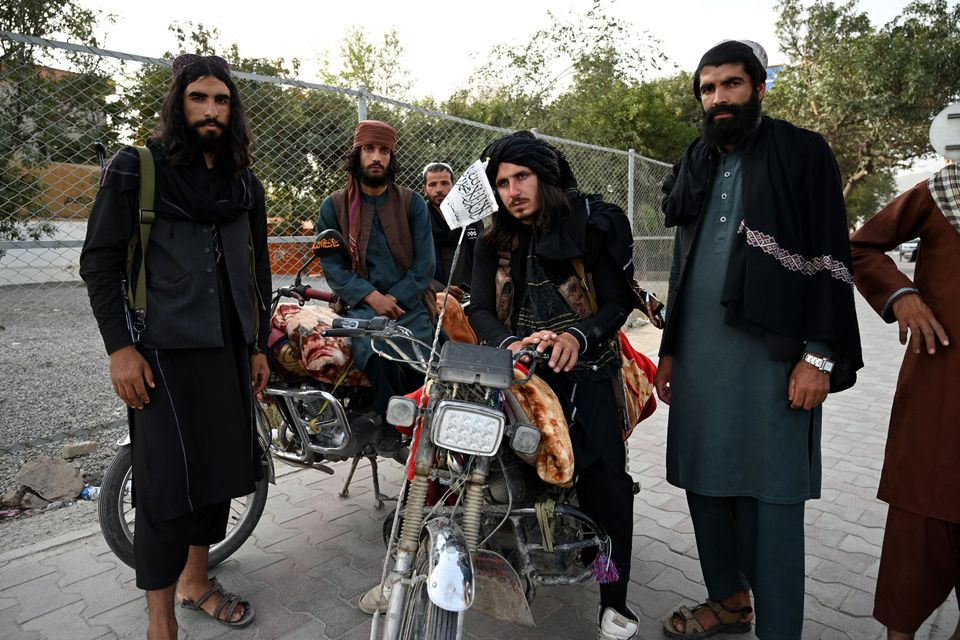 Taliban fighters stand along a road in Kabul on August 18, 2021, after the Taliban's military takeover...