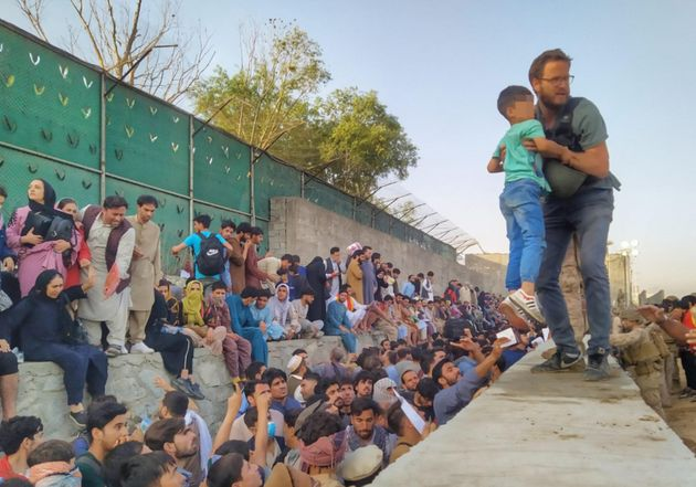The work of the Italian consul in Kabul, Tommaso Claudi, who for days has been engaged in the evacuation of fellow citizens and Afghans from the country returned to the Taliban, does not stop, Kabul (Afghanistan), 23 August 2021. In some photos that have gone viral on social media, he can be seen while he helps a child, frightened by the crowd and in tears, to overcome a wall in the inner perimeter of the airport, where people are crowded waiting for a flight to escape. Bulletproof vest and helmet over the shoulder, Claudi lifts the child of the apparent age of 6-7, taking him from the arms of a man who hands it to him and thus taking him away from the crowd of waiting people - including women and children - under the watchful gaze of a soldier. FARNESINA PRESS OFFICE +++ ANSA PROVIDES ACCESS TO THIS HANDOUT PHOTO TO BE USED SOLELY TO ILLUSTRATE NEWS REPORTING OR COMMENTARY ON THE FACTS OR EVENTS DEPICTED IN THIS IMAGE; NO ARCHIVING; NO LICENSING +++