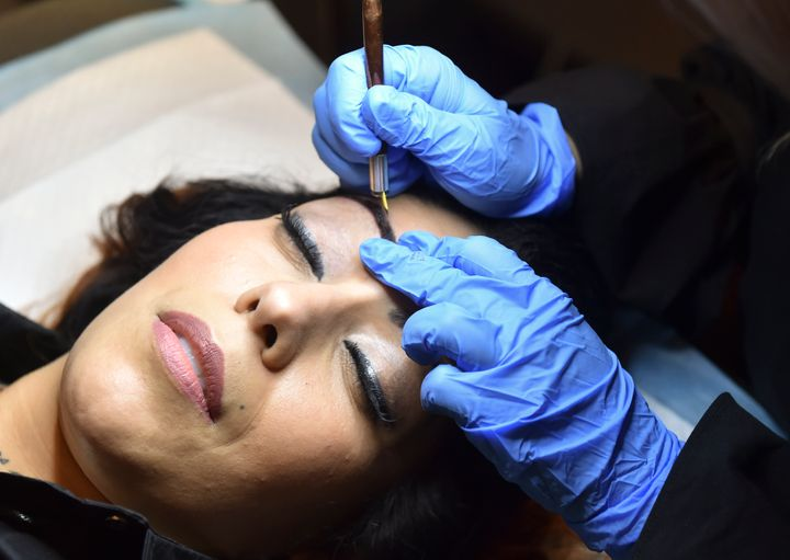 A woman gets her brows microbladed.