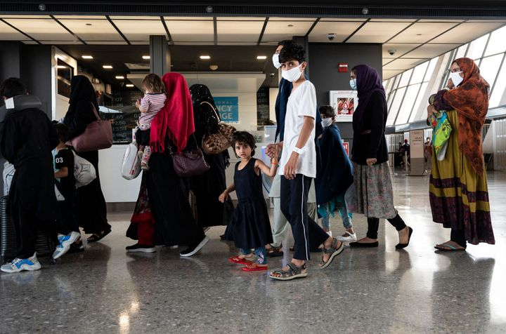 Afghan refugees are escorted to a waiting bus after arriving and being processed at Dulles International Airport on Aug. 23.