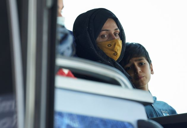 An Afghan woman and boy sit on a bus taking them to a refugee processing center upon arrival at Dulles International Airport in Dulles, Virginia, U.S., August 24, 2021. REUTERS/Kevin Lamarque