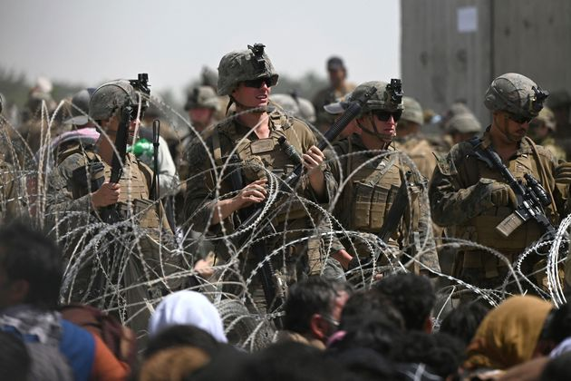TOPSHOT - US soldiers stand guard behind barbed wire as Afghans sit on a roadside near the military part...
