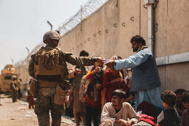 A Marine with the 24th Marine Expeditionary unit (MEU) passes out water to evacuees during the evacuation...