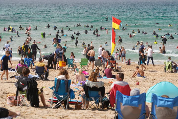 Holiday-makers on Fistral Beach on August 19, 2021 in Newquay, Cornwall, England.