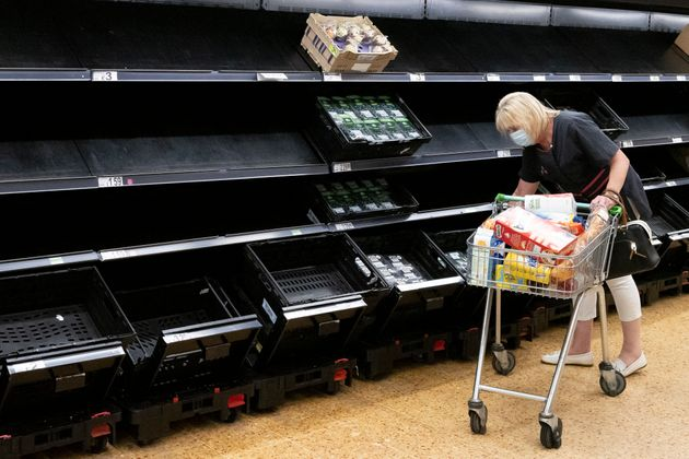 A woman wearing a face mask near empty fruit and veg shelves in an ASDA store on July 23, 2021 in Cardiff,...