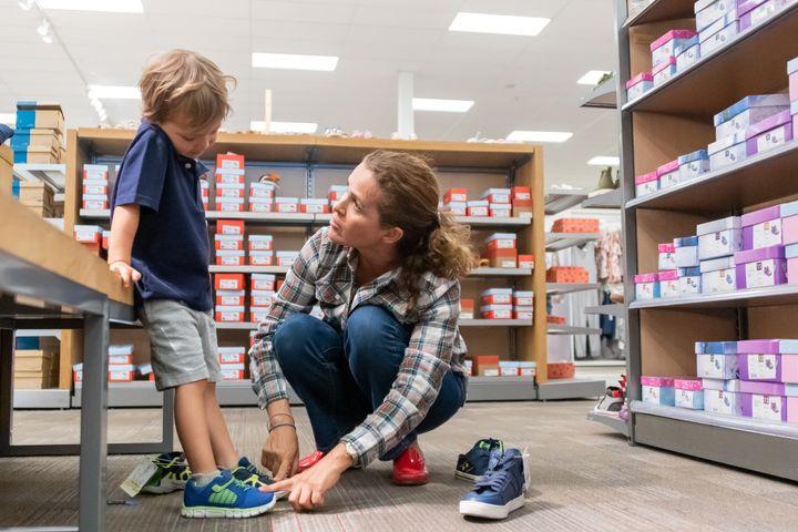 Una mujer comprando zapatos para su hijo en una tienda.