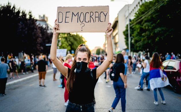 Young woman protester holding placard with text