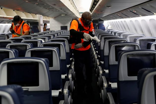 Delta Air Lines pre-flight cleaning crew members use electrostatic disinfection devices to clean an aircraft at JFK International Airport in New York, U.S., August 6, 2020. Picture taken August 6, 2020. REUTERS/Shannon Stapleton