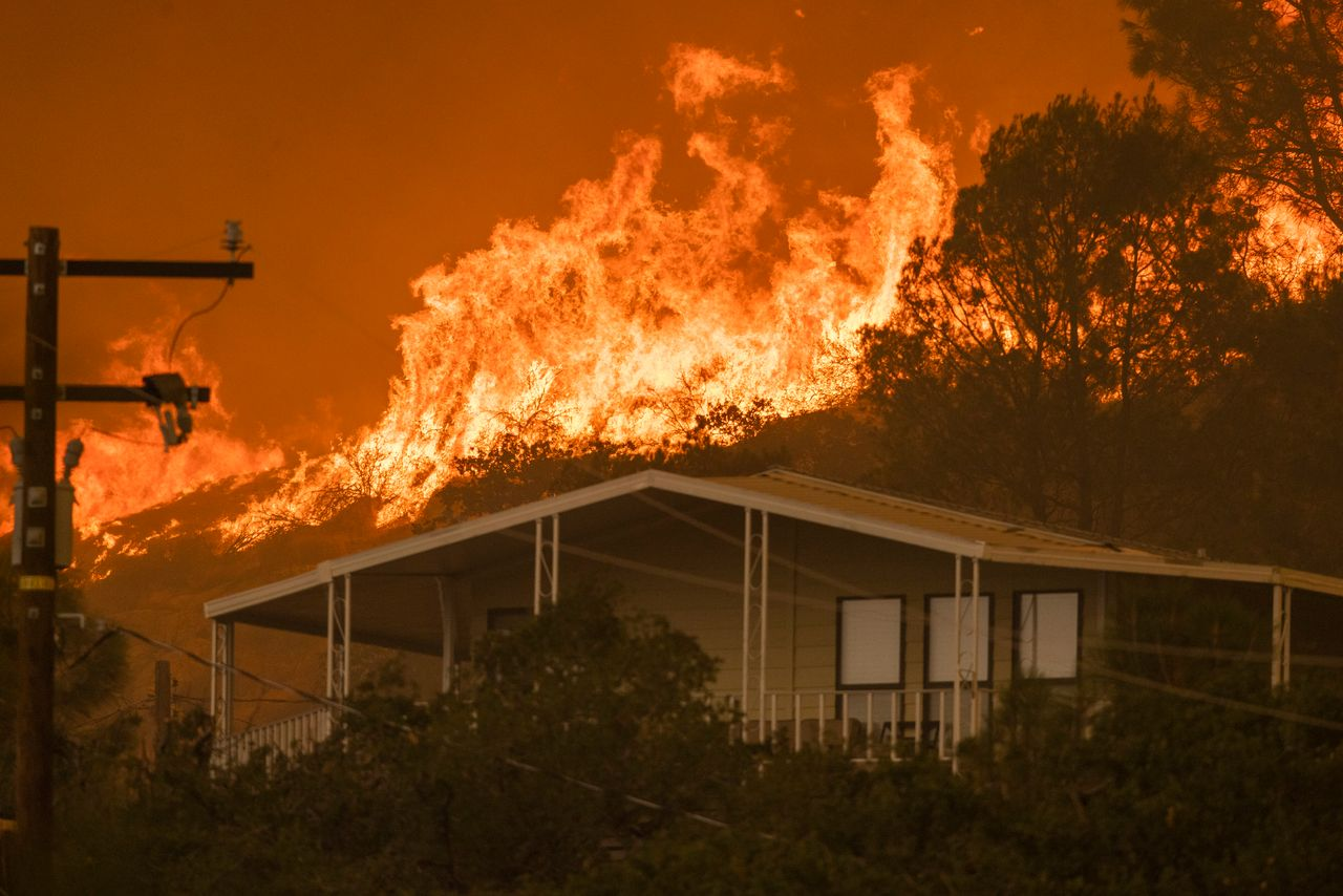 A wildfire approaches homes on Aug. 24 in Wofford Heights, California.
