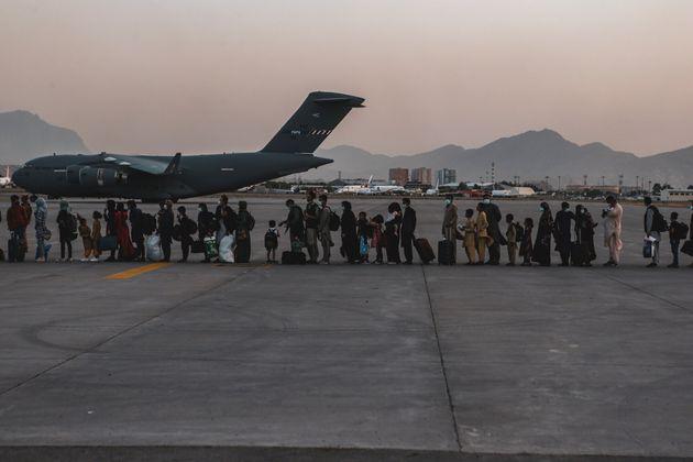 Evacuees wait to board a Boeing C-17 Globemaster III during an evacuation at Hamid Karzai International...