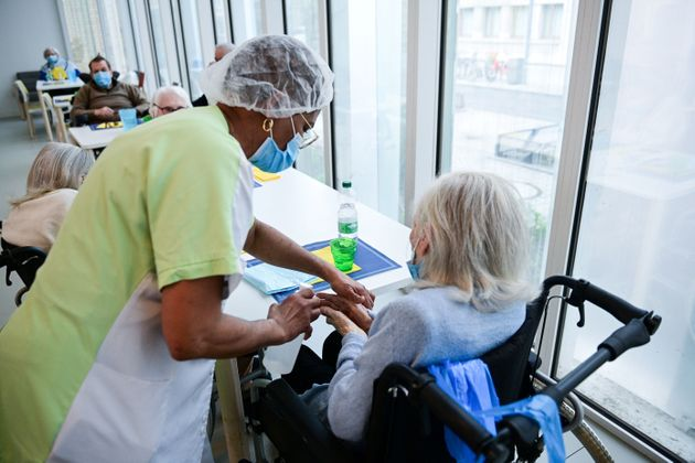 A nurse provides hydro-alcoholic gel to residents at the Alice Prin EHPAD (Housing Establishment for Dependant Elderly People) in Paris, on March 4, 2021. (Photo by Martin BUREAU / AFP) (Photo by MARTIN BUREAU/AFP via Getty Images)