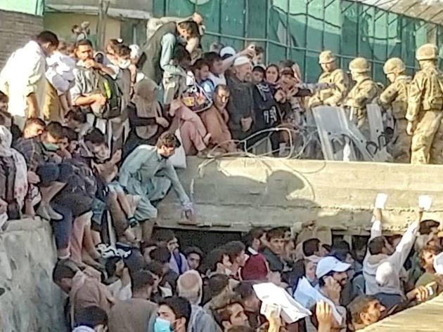 Security personnel assist with evacuation of the people waiting outside the airport in Kabul, Afghanistan August 25, 2021 in this picture obtained from social media. Twitter/DAVID_MARTINON via REUTERS