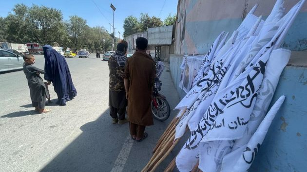 KABUL, AFGHANISTAN - AUGUST 26: Flags of Taliban distributed to people near the evacuated US Embassy in Kabul, Afghanistan, on August 26, 2021. (Photo by Haroon Sabawoon/Anadolu Agency via Getty Images)