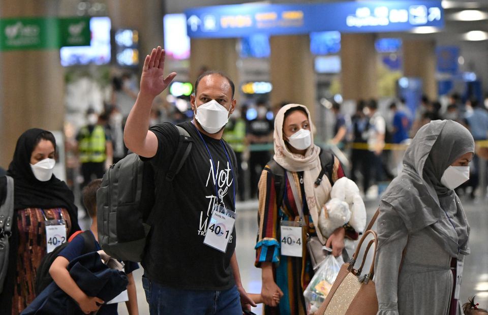 Afghan evacuees arrive at Incheon International Airport outside Seoul on August 26, 2021, following their...