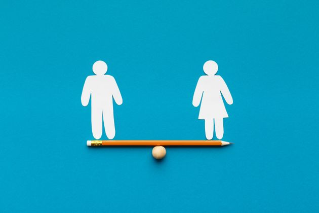 Gender equality in corporate world. Figures of man and woman on pencil seesaw, blue background, copy space