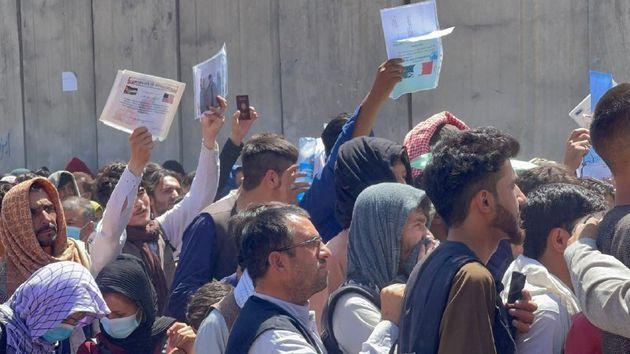 Numerosos afganos esperan en torno al aeropuerto Hamid Karzai de Kabul, enseñando sus documentos...