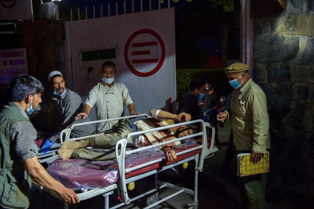 EDITORS NOTE: Graphic content / Medical and hospital staff bring an injured man on a stretcher for treatment after two powerful explosions, which killed at least six people, outside the airport in Kabul on August 26, 2021. (Photo by Wakil KOHSAR / AFP) (Photo by WAKIL KOHSAR/AFP via Getty Images)