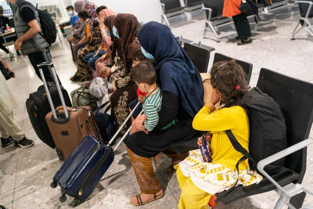 Refugees from Afghanistan wait to be processed after arriving on an evacuation flight at Heathrow Airport...