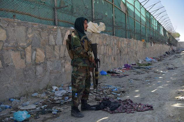 A Taliban fighter stands guard at the site of the August 26 twin suicide bombs, which killed scores of...