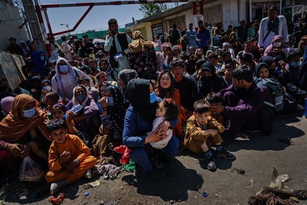 Women and children are made to crouch and wait outside the Taliban controlled check point near the airport's...