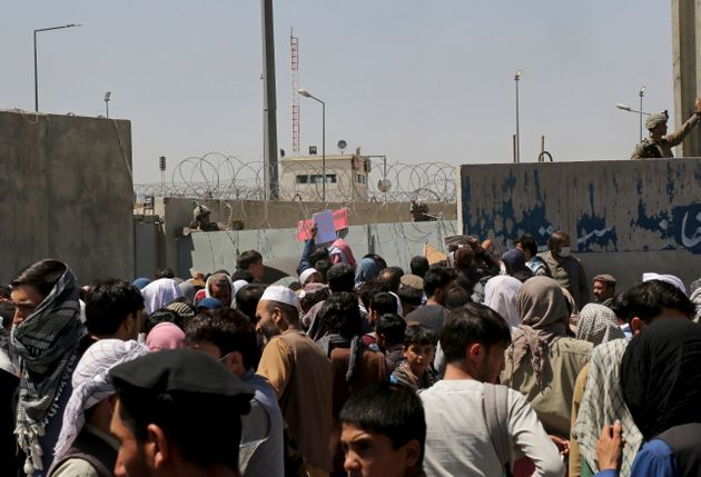 US soldiers stand inside the airport wall as hundreds of people gather near an evacuation control checkpoint...