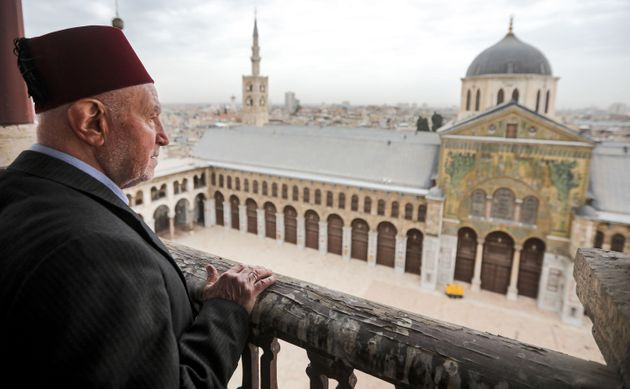 Mohammad Ali al-Sheikh, the eldest of the Muezzins who call Muslims to prayer, stands on a balcony of the Umayyad Mosque in the ancient quarters of Damascus on March 12, 2020. - Inside the Syrian capital's Great Umayyad Mosque, six muezzins sit before a loudspeaker, collectively reciting the call to prayer, their voices filling the air above the ancient quarters of Damascus. They are among 25 muezzins who take shifts intoning the azan, or call to prayer, in groups using a technique of collective recital that is unique to the centuries-old mosque. (Photo by LOUAI BESHARA / AFP) (Photo by LOUAI BESHARA/AFP via Getty Images)