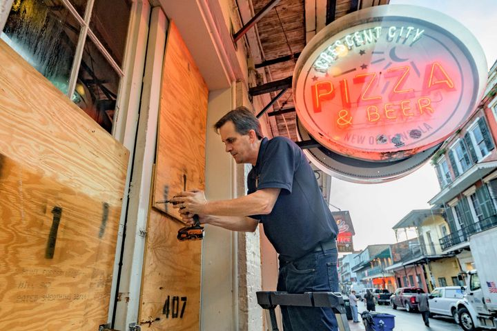 Michael Richard of Creole Cuisine Restaurant Concepts boards up Crescent City Pizza on Bourbon Street in the French Quarter before landfall of Hurricane Ida in New Orleans, Saturday, Aug. 28, 2021.