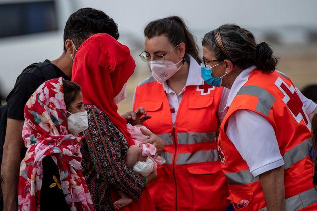 Dos cooperantes de Cruz Roja atienden a una madre afgana y su bebé en Torrejón de Ardoz
