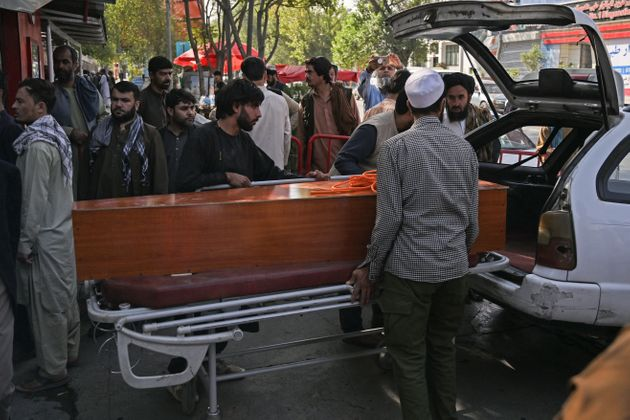 Relatives load in a car the coffin of a victim of the August 26 twin suicide bombs, which killed scores of people including 13 US troops outside Kabul airport, at a hospital run by the Italian NGO Emergency in Kabul on August 27, 2021. (Photo by Aamir QURESHI / AFP) (Photo by AAMIR QURESHI/AFP via Getty Images)
