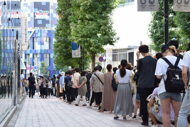 新型コロナウイルスワクチンの接種会場前で並ぶ若者たち