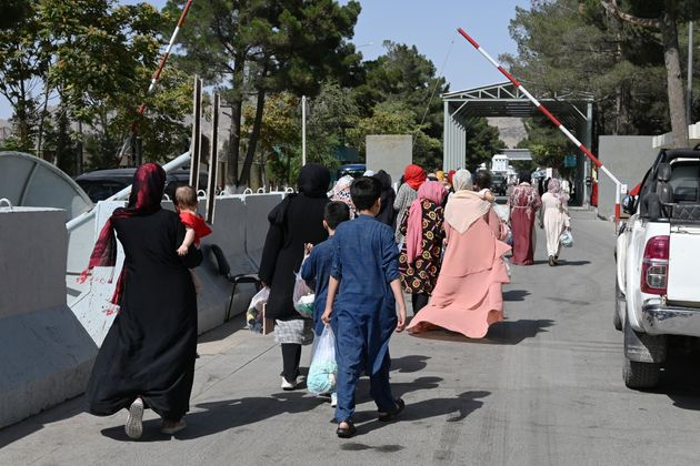 Afghans, hoping to leave Afghanistan, walk through the main entrance gate of Kabul airport in Kabul on...